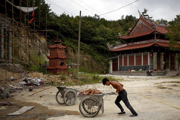 9月28日,福建泉州附近,石神伟正在运送建筑材料。