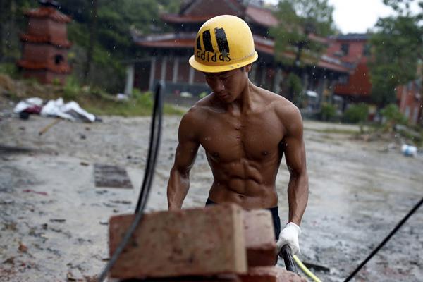 9月28日,石神伟正在用独轮车运送砖块。