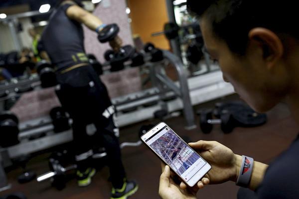 10月5日,北京,健身教练毕先生正在观看石神伟的健身视频。