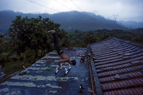 9月28日,福建,石神伟在工地宿舍的屋顶健身,如今他也会使用一些专业的健身器材来锻炼。