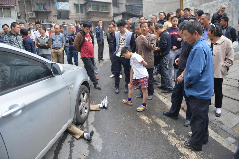 图为男子在车底不起来,只有双脚露出车外。