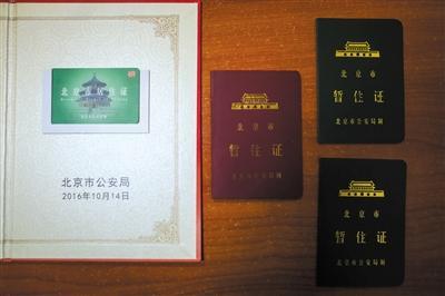 吴先生展示自己的居住证和以前的暂住证。