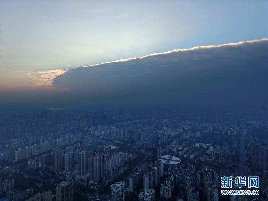 """10月15日,南昌红谷滩上空,天空被一分为二。当日,江西南昌出现罕见的""""阴阳天""""气候现象。天空中有一条明显的线条,将天空一分为二:一边是云层,一边是蓝天。新华社记者 周密 摄"""