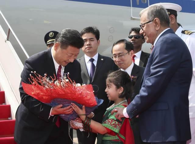 图为10月14日,国家主席习近平抵达达卡,开始对孟加拉人民共和国进行国事访问。这是习近平接受孟加拉国儿童献花。(新华社记者兰红光摄)
