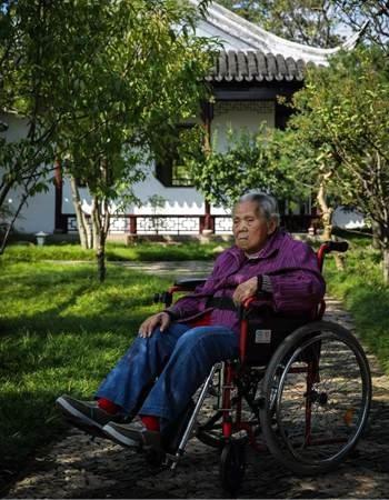 10月11日,梁金玉坐在轮椅上,轮椅扶手曾经磨得发亮,一些金属布局上,油漆班驳脱落,显露锈迹。新京报记者 彭子洋 摄
