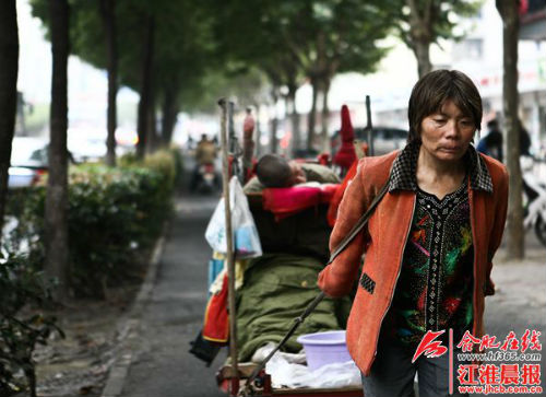 刘从花拉着丈夫和板车在合肥街头乞讨寻医,从不埋怨,只想治好丈夫的病。