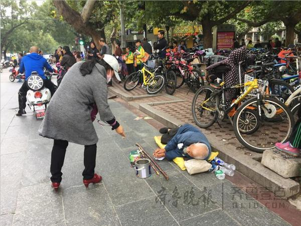 泰安一中北临,一名乞丐躺在地上,来往市民不时地给他施舍一些零钱。
