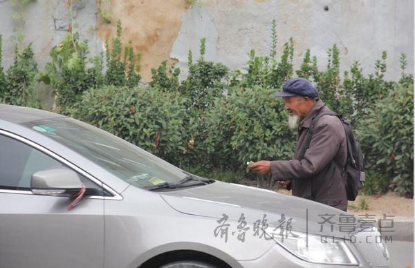 泰安龙潭路和灵山大街交口附近,一名乞讨者正在拦车乞讨。