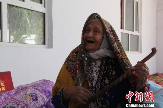 """经医院检查,今年130岁高龄的世界最长寿老人阿丽米罕?色依提,没有""""三高"""",健康状况很好。图为老人用拐杖当乐器唱歌。 朱景朝 摄"""