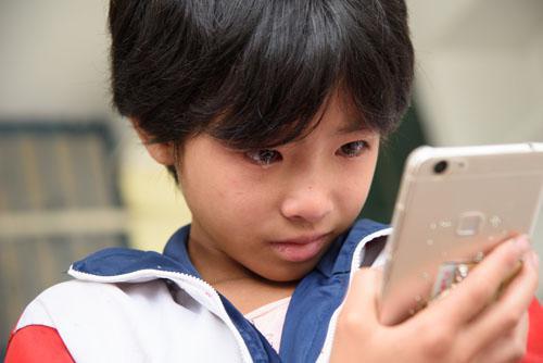 贵州毕节市黔西县绿化乡的留守儿童李淑银和外出打工的父亲视频聊天后哭泣(2016年9月13日摄)。新华社发