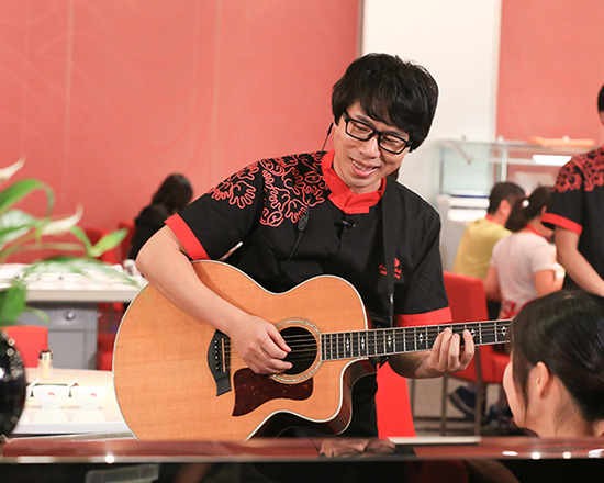 卢庚戌在海底捞弹吉他为客人服务