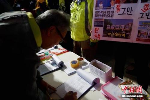 """10月29日晚,近两万名韩国民众及民间团体人士在首尔市中心举行烛光集会,谴责""""亲信干政事件""""给韩国社会带来的不良影响,要求总统朴槿惠对此事负责。图为民众在集会现场写下请愿书,要求查明事情真相。中新社记者 吴旭 摄"""
