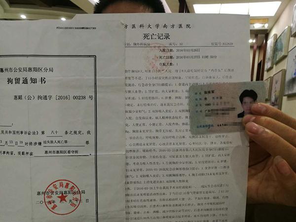 亲属手持张味军的拘留通知书和死亡记录。
