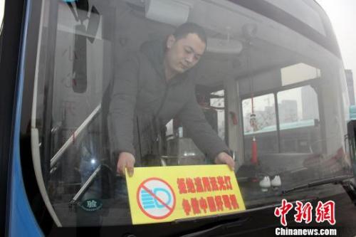 """资料图:一名郑州4路公交车车长将印有""""拒绝滥用远光灯争做中国好司机""""的宣传展板放在车辆前挡风玻璃上,时刻提醒自己文明行车。 周小云 摄"""