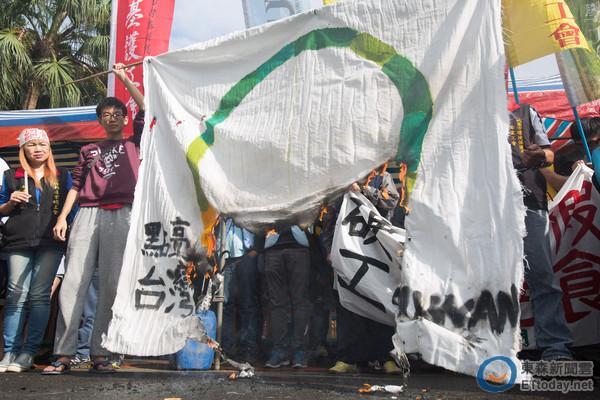 """工斗团体焚烧蔡英文竞选""""点亮台湾""""旗。(图片来源:台湾东森新闻云)"""