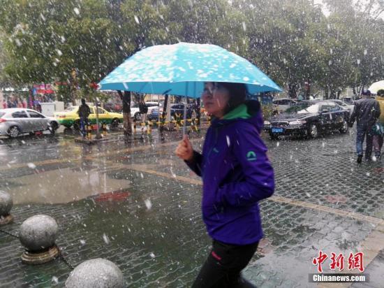 资料图:10月19日12时许,乌鲁木齐的降雨突然变成漫天的雪花,截至15时许,降下鹅毛般大雪,来势汹汹,气温降至零度以下。乌鲁木齐明园BRT车站附近看到,女性打着伞、穿着厚衣服,以抵御寒风和降雪的侵袭。中新社记者 王小军 摄