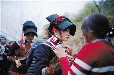 新娘勒尔拉则换上彝族婚礼服装,戴上首饰。