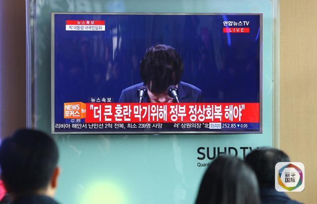 11月4日,在韩国首尔火车站,人们观看总统朴槿惠对国民讲话的电视直播。 (新华社记者姚琪琳摄)