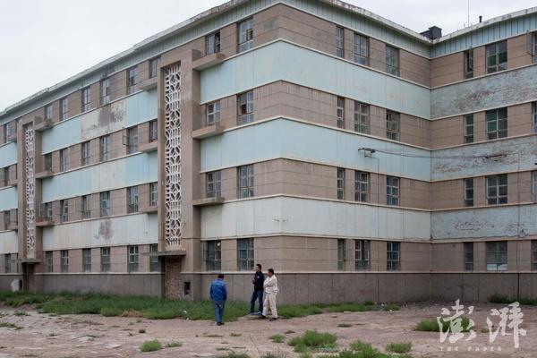 偶有中年男子三三两两地在楼底转角抽烟,他们的身后是废弃的楼房。