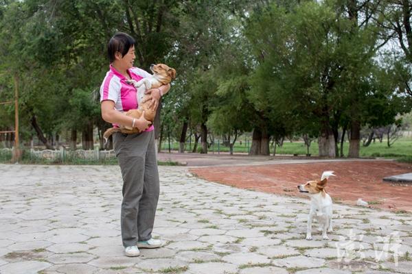 一名当地职工家属在跟她饲养的狗狗讲话。