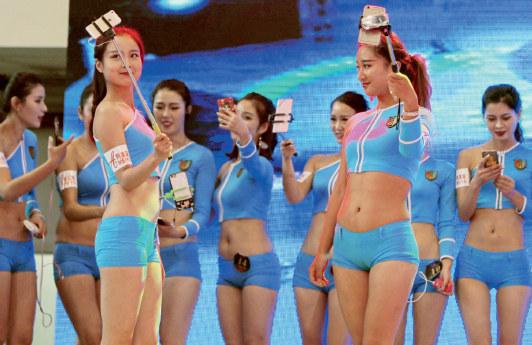 """11 月6 日,""""河南首届网红直播模特大赛""""在郑州举行。大赛决赛期间,收集美男主播们身着性感比基尼,在T 台上现场""""开直播""""、走模特步。CFP"""