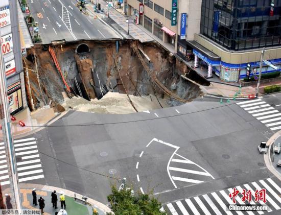 当地时间2016年11月8日,日本福冈,JR博多站附近的十字路口公路忽然塌陷,出现一个大坑,导致交通混乱及停电。