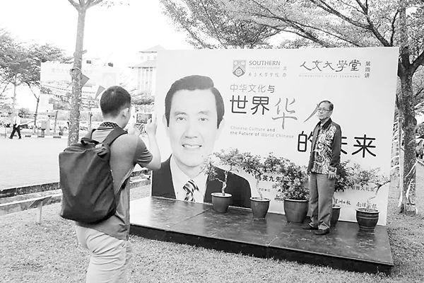 一位女子在马英九演讲海报前留影。俞懿春/摄
