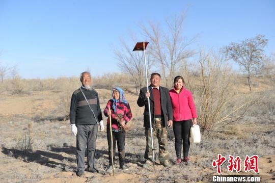 """在基本生存条件都难以保障的中国腾格里沙漠腹地,76岁的王天昌和他48岁的儿子王银吉携家带口坚守了30多年,通过人力造成7500亩(约合680个标准足球场)沙漠""""绿洲""""。图为王天昌一家两代四口人。 杨艳敏 摄"""