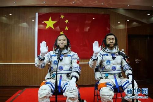 10月17日,神舟十一号航天员出征仪式在酒泉卫星发射中心举行。这是航天员景海鹏(左)、陈冬在出征前挥手。 新华社记者李刚摄 新华网