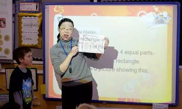 来自上海的卢老师(音)正在给英国肯辛顿福克斯小学的三年级学生讲解分数。(英国《卫报》)