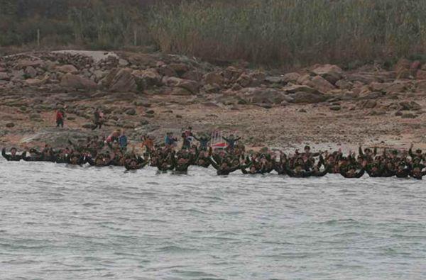 朝鲜最高领导人金正恩视察了位于朝鲜西南前线水域最南端的葛里岛前哨基地和长在岛防御队。图为金正恩视察前哨基地和防御队。官兵们又跳下海迎接。