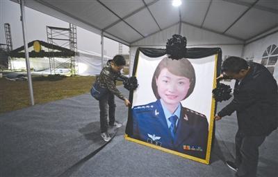 17日,崇州市体育中心,工作人员正在布置烈士余旭的遗像,余旭的公祭活动将在此举行 成都商报摄影记者 王勤