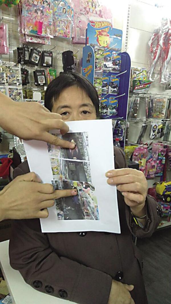 东家官老师的母亲在展现打印进去的监控截图,监控拍下了偷拿货色的小伴侣。 重庆商报 图