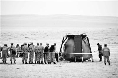 11月18日,工作人员在对返回舱进行处置 供图/新华