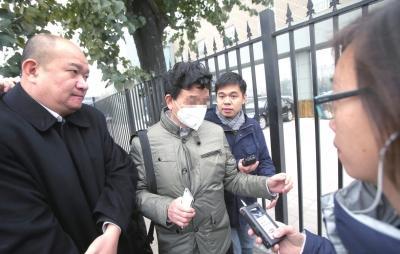 今天李某的父�H(戴口罩者)�淼绞腥�中院旁���理。