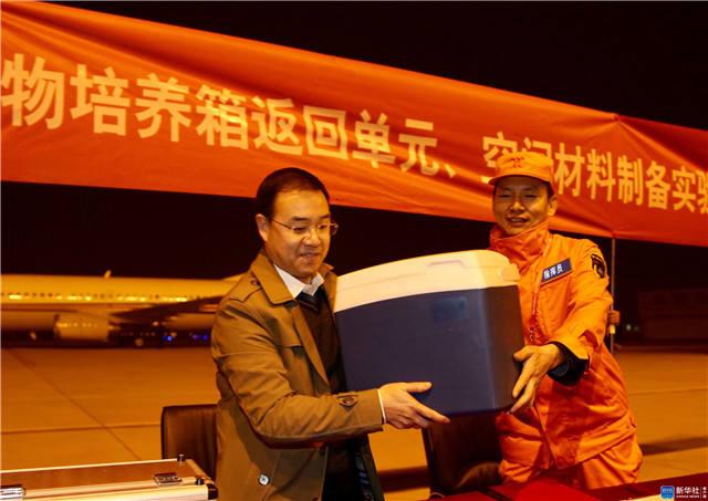 11月18日,在北京西郊机场,空间应用系统副总设计师吕从民(左)从西安卫星测控中心回收部总工程师冀刚(右)手中接过高等植物培养箱返回单元和空间材料制备实验样品。新华社记者 金立旺