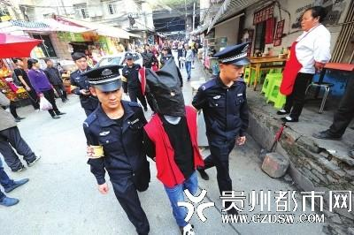 民警押着嫌疑人指认现场。