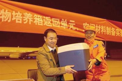 11月18日,在北京西郊机场,空间应用系统副总设计师吕从民(左)从西安卫星测控中心回收部总工程师冀刚(右)手中接过高等植物培养箱返回单元和空间材料制备实验样品。