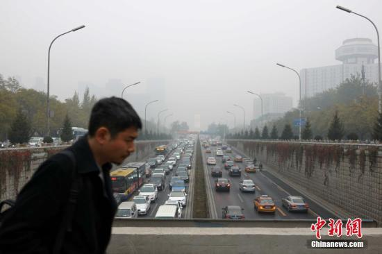 资料图 11月18日,受不利气象条件影响,北京遭遇持续空气重污染。北京市于17日0时启动空气重污染橙色预警,这也是今年北京首次启动空气重污染橙色预警。 中新社记者 韩海丹 摄