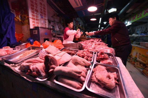 资料图:中国市民在农贸市场内购买猪肉。新华社记者 张楠 摄