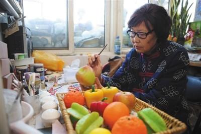 昨天,西城区非物资文明遗产蜡果制造传承人刘秀华的家中,刘秀华正在制造瓜果蔬菜。