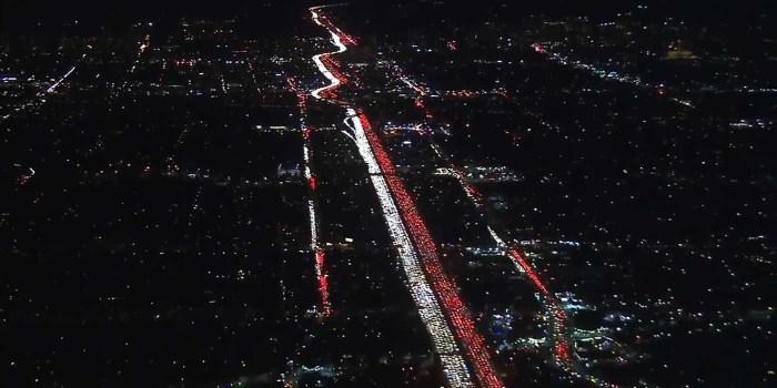 美国ABC7 Eyewitness News用航拍机拍下这一幕:一侧是前灯的白,一侧是尾灯的红,一白一红更像是为圣诞节预热。