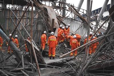 昨日,救援人员在事故现场搜寻被困者。