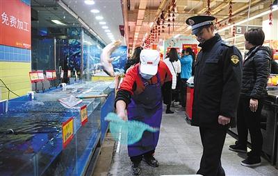 通州卜蜂莲花超市,一名超市员工现场宰杀捞出的淡水鱼。