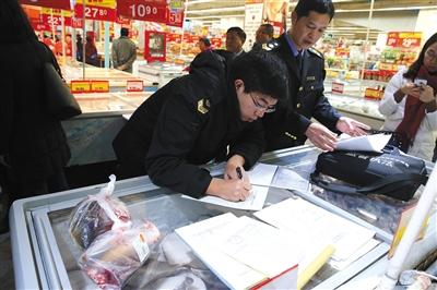 通州卜蜂莲花超市,食药监局工作人员将超市里现捞的淡水鱼装袋登记,准备带回实验室检测。