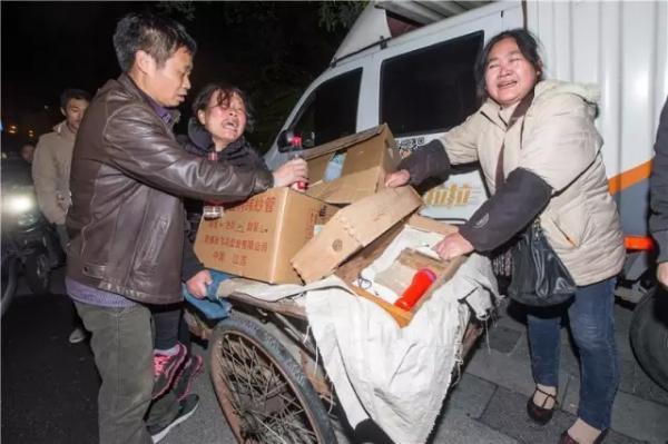 邱老板(左)一家在火场外痛哭,他们是龙游人,仓库里堆着他们的织布机配件,是几十年的心血,而他们用三轮车抢救出了一堆账本。 记者 陈中秋 图