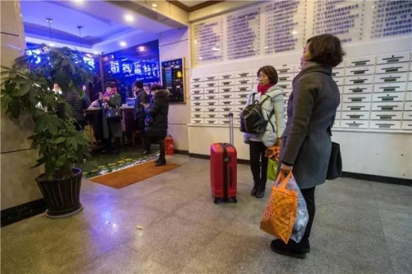 紧邻火场的一家宾馆,住客纷纷退房离开。 记者 陈中秋 图