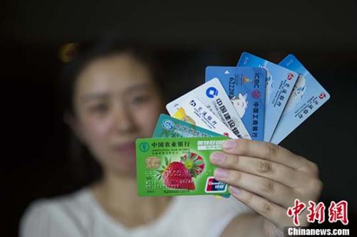 材料图:山西太原,大众展现银行卡。 中新社记者 张云 摄