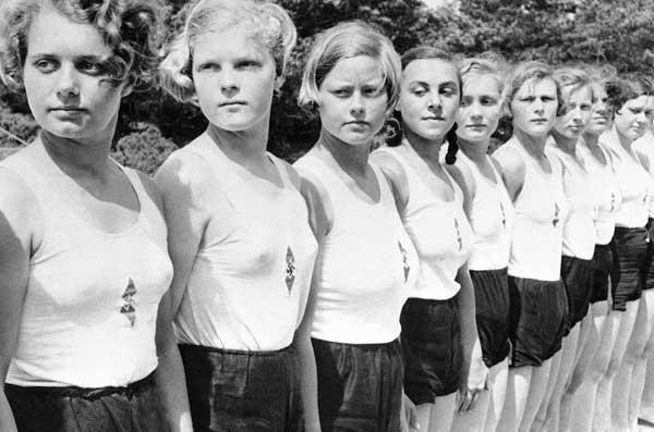 1936年2月24日,德国柏林,少女队成员站成一排学习音乐。
