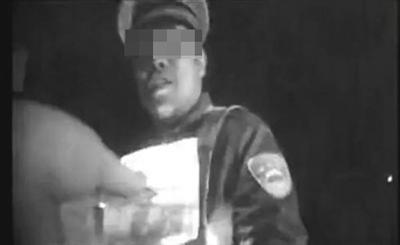 一位身穿交警礼服和反光背心的女子,在收受一位货车司机递来的百元钞票。视频截图